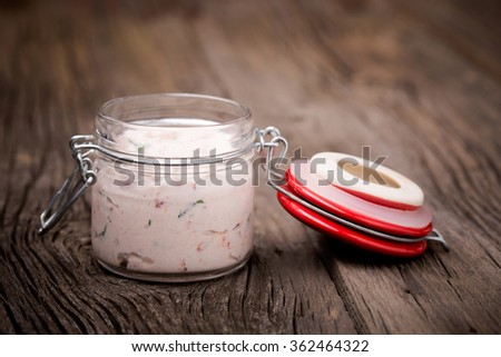 Homemade DIY natural vegetarian very healthy dried tomatoes, basil, chilli and ricotta paste in a glass jar on a wooden table - stock photo