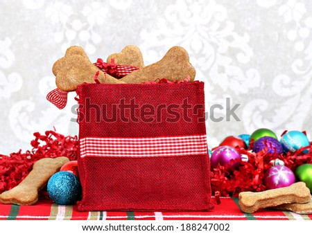 Homemade dog biscuits, shaped like bones, fill a festive Christmas bag.  Healthy, homemade treats for a dog's Christmas. - stock photo