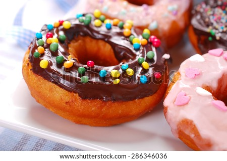 homemade donuts with chocolate and icing glaze and colorful sugar sprinkles  - stock photo