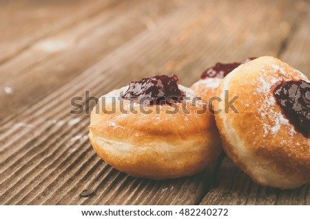 Homemade donuts with jam on wooden table