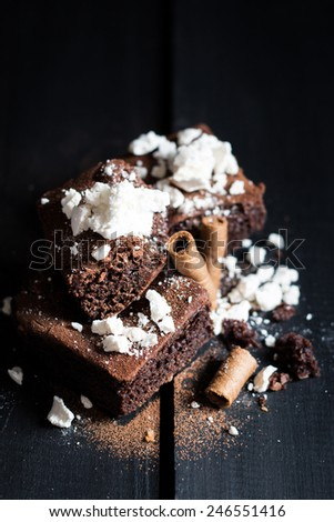 Homemade Double Chocolate Cake with Crushed Meringues and Wafer Rolls. Dark Wooden Table Background. Moody Atmosphere - stock photo