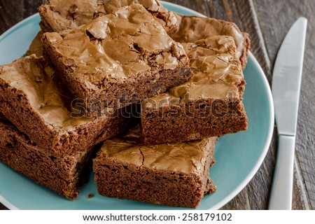 Homemade double chocolate chunk brownies stack on bright blue plate sitting on wooden table with knife - stock photo
