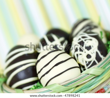 homemade easter eggs in a basket. Dark and white chocolate. Green lined background with very shallow depth of field. - stock photo