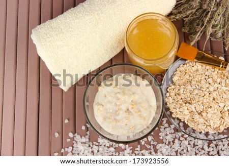 Homemade facial mask with oats and honey,on color wooden background - stock photo