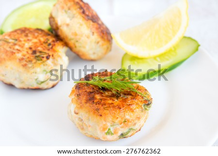 Homemade fish cakes with dill and lemon on white plate - stock photo