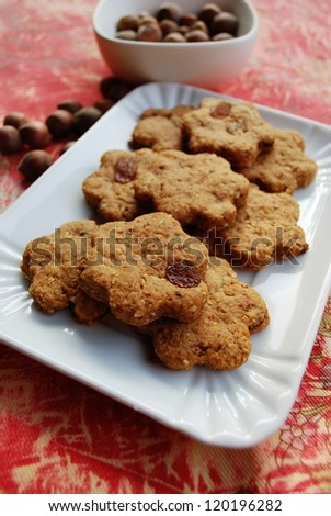 Homemade flower shaped cinnamon cookies with whole wheat, raisins and hazelnuts - stock photo