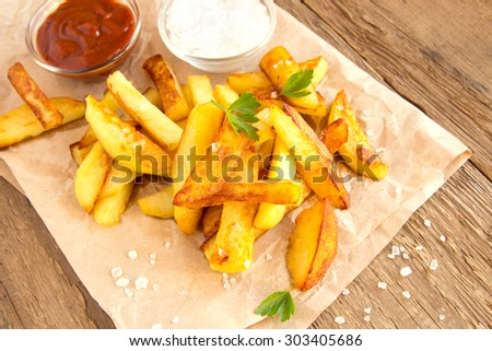 Homemade french fries (fried potatoes) with sea salt, parsley and ketchup on rustic wooden background