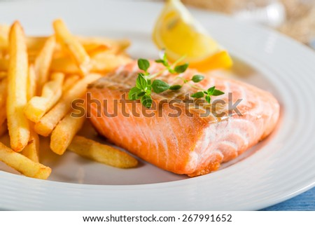 Homemade french fries with salmon served on plate - stock photo