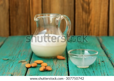 Homemade fresh almond milk in glass jar with empty glass bowl and whole almonds on shabby turquoise wooden table - stock photo