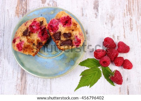 Homemade fresh baked muffins with chocolate and raspberries on old rustic wooden board, delicious dessert - stock photo