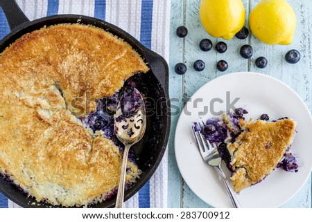 Homemade fresh blueberry cobbler baked in cast iron skillet pan with piece on white plate and whole blueberries and lemons - stock photo