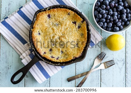 Homemade fresh blueberry cobbler baked in cast iron skillet pan with piece on white plate and with bowl of blueberries, lemon and forks - stock photo
