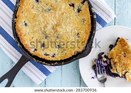 Homemade fresh blueberry cobbler baked in cast iron skillet pan with piece on white plate with fork - stock photo