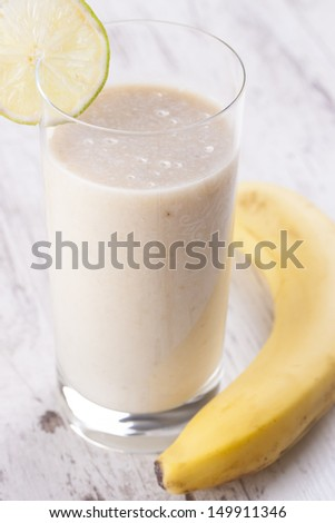 Homemade fresh mixed up glass of banana juice on a bright wooden background