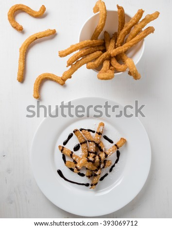 homemade fried churros dessert on white plate with chocolate - stock photo