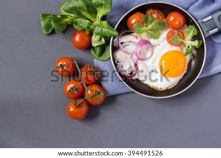 Homemade fried eggs served in frying pan with tomatoes, herbs, onion. Top view with copy space - stock photo