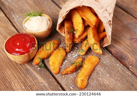 Homemade fried potato in paper bag, on wooden background - stock photo