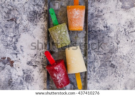Homemade frozen colored fruit juice or ice pop on a tray. Top view. Rustic style. - stock photo