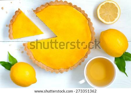 Homemade fruit lemon tart pie with green tea on white rustick table background - stock photo