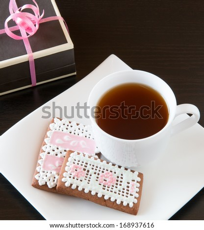 Homemade gingerbread cookies and cup of tea with gift. - stock photo