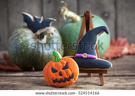 Homemade gingerbread cookies in the form of a halloween witch hat with jack-o-lantern pumpkin and a bat on a autumn background. Space for text and selective focus on the hat. - stock photo
