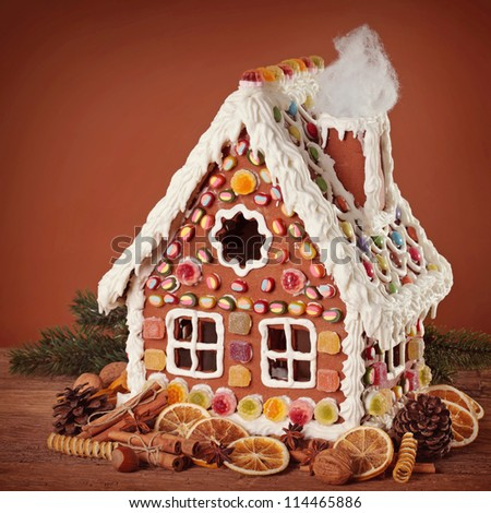 Homemade gingerbread house on brown background - stock photo