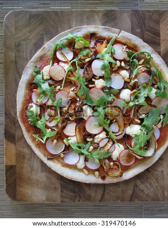 Homemade gluten free pizza crust with radishes, arugula, pine nuts and caramelized onions - stock photo