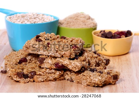 Homemade granola bars with ingredients in measuring cups in the background - stock photo