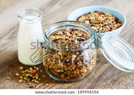 Homemade granola in open glass jar and milk or yogurt  on rustic wooden background - stock photo
