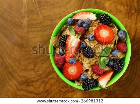 homemade granola muesli with berries (strawberries, raspberries, blueberries) for breakfast - stock photo