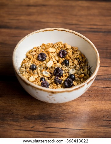 Homemade granola or muesli with oat flakes, corn flakes, dried fruits and toasted peanuts with fresh berries in a bowl for breakfast, selective focus - stock photo
