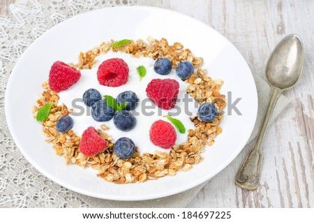 homemade granola with yogurt, raspberries and blueberries on the plate