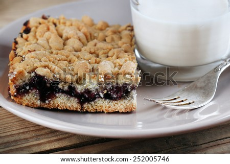 Homemade grated pie with jam and glass of milk on wooden background - stock photo