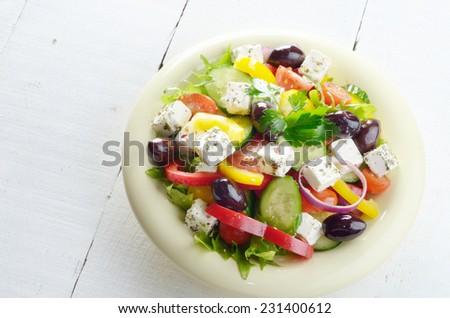 Homemade greek salad on white table - stock photo