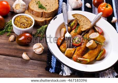 Homemade grilled sausages with vegetables on a wooden background. Selective focus.