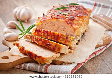 Homemade ground meatloaf with ketchup and rosemary - stock photo
