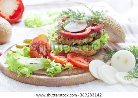 Homemade hamburger on white plate, sliced tomatoes, onion, pepper, lettuce and dill on wooden board, tomatoes souse in ceramic plate. White wooden table.