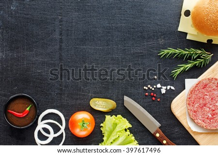 Homemade hamburger recipe. Raw minced beef (patty), fresh bun, slice of cheese, tomato, onion rings, pickle, lettuce, herbs and BBQ sauce. Black board background. Space for text. - stock photo