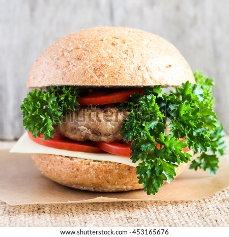 Homemade hamburger with tomatoes, cheese and fresh parsley, selective focus - stock photo
