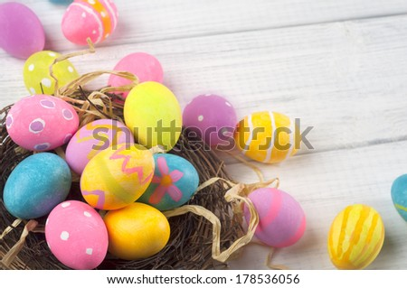 Homemade Hand Painted Easter Eggs of Various Colors in a Nest on White Board Background with room or space for copy, text, words. - stock photo