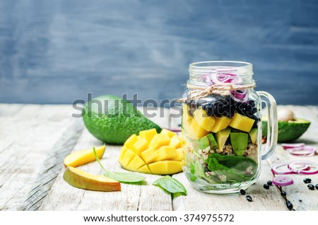 homemade healthy salads with black beans, vegetables, fruits, and quinoa in jar. toning. selective Focus - stock photo
