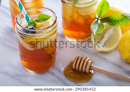 Homemade honey iced tea in mason jars with straws - stock photo