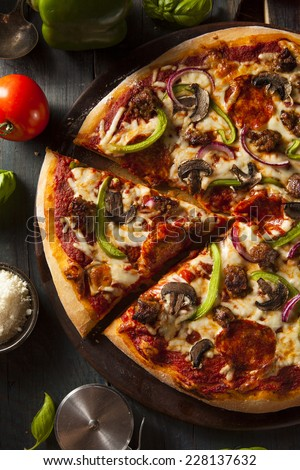 Homemade Hot Supreme PIzza with Pepperoni Peppers and Sausage - stock photo
