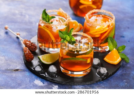 Homemade ice tea with lemon, lime, orange, ice cubes and fresh mint on blue wooden background, selective focus - stock photo