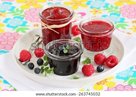 Homemade jams ( blueberry,raspberry,strawberry) and fresh berries.Selective focus. - stock photo
