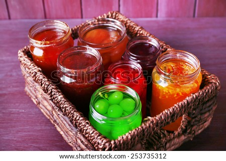 Homemade jars of fruits jam in wicker basket and color wooden background - stock photo