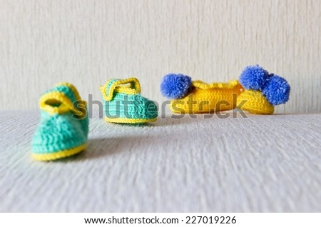 Homemade knitted small baby wool shoes. Two couple. Selective focus - stock photo