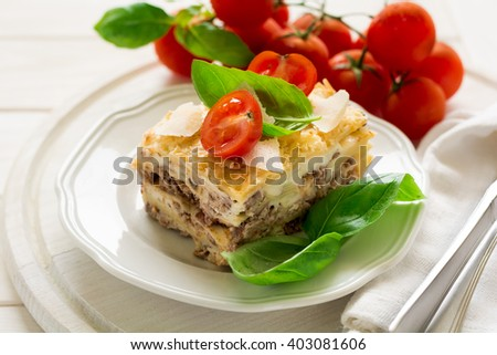 Homemade lasagna with bechamel sauce decorated basil leaves and cherry tomatoes on white plate - stock photo