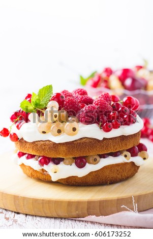 Homemade  layer cake with berries on white rustic wooden table
