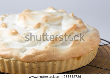 Homemade lemon meringue pie, a classic of European dessert cuisine, on a cooling rack fresh from the oven - stock photo